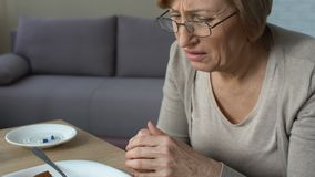 Senior lady feeling heaviness and stomach pain after eating pie, pills on table
