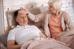 Senior lady feeling temperature of her sick husabnd Stock Image