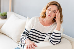 Senior lady feels pain in head. Mature woman is suffering from headache. She is sitting on sofa and touching temple. Her eyes are closed with frustration stock photo