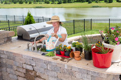 Senior lady filling a watering can on a patio Stock Photos
