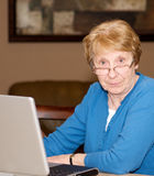 Senior lady frustrated with computer. Senior woman at the computer with a frustrated expression Stock Photo