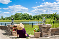 Senior lady gardener taking a break. To admire the view from her front patio over a lake and lush green countryside sitting with her back to the camera in a stock photo