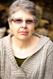 Senior Lady with Glasses. Portrait of a somber senior gray haired lady wearing glasses.  Shallow depth of field Royalty Free Stock Photo