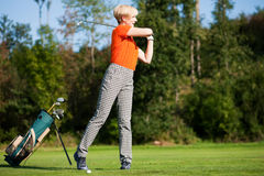 Senior lady golfer. Senior female golfer doing a golf stroke, she is playing on a wonderful summer afternoon Royalty Free Stock Images
