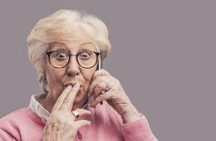 Senior lady gossiping on the phone. Funny senior lady having a phone call on her smartphone and gossiping, she is surprised and excited royalty free stock photos