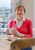 Senior lady having  breakfast in   cafe. Royalty Free Stock Photo