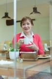 Senior lady having  breakfast in   cafe. Stock Photography