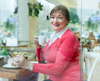 Senior lady having  breakfast in   cafe. Royalty Free Stock Photo
