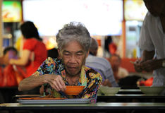 Senior lady having a meal in a hawkers center. SINGAPORE/SINGAPORE - CIRCA NOVEMBER 2015: Senior lady eating a soup in a hawkers center stall in Singapore's stock images