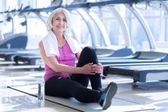 Senior lady having pause at gym. Little break. Portrait of attractive elderly happy woman sitting on carry mate at fitness studio while having pause Royalty Free Stock Photography