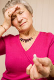 Senior lady with headache holding tablet or pill Royalty Free Stock Photo