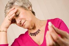 Senior lady with headache holding tablet or pill Stock Photos
