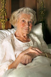Senior lady in her nightgown in bed. Sitting propped up comfortably against her pillows smiling at the camera Royalty Free Stock Images