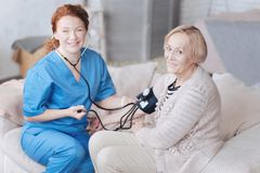 Senior lady and her nurse smiling while measuring pressure. Positivity is healing. Top view of a cheerful elderly patient and a female caregiver sitting on a Stock Image
