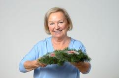 Senior lady holding a Christmas decoration Stock Image
