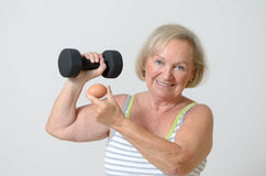 Senior lady holding a dumbbell and egg Royalty Free Stock Photo