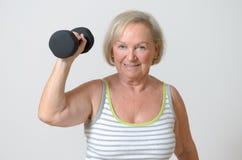 Senior lady holding a dumbbell Stock Image