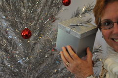 Senior lady holding shaking Christmas gift Stock Photography
