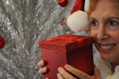 Senior lady holding red Christmas gift box stock photo