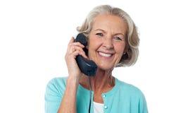 Senior lady holding phone receiver Stock Image