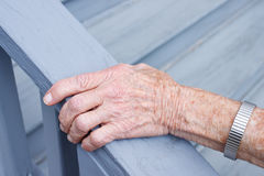 Senior lady holding stair rail. In porch royalty free stock photography