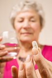 Senior lady holding tablet or pill with water Royalty Free Stock Photos