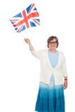 Senior lady holding UK flag and waving. Isolated on white Royalty Free Stock Image