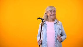 Senior lady holding walking stick, disability aids for elderly, healthcare. Stock photo stock photography