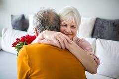 Senior lady hugging her husband holding bunch of roses. Portrait of senior lady hugging her husband holding bunch of roses Stock Photo