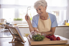 Senior lady in the kitchen. Everything must be done by the recipe Stock Images