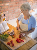 Senior lady in the kitchen Royalty Free Stock Photos