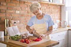 Senior lady in the kitchen Royalty Free Stock Photos