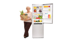Senior lady leaning on a fridge. Senior lady holding a grocery bag and leaning on an open refrigerator isolated on white background stock images