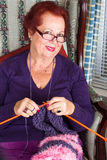 Senior Lady looking at You While Knitting Royalty Free Stock Image
