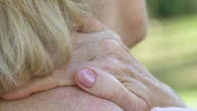 Senior lady massaging neck and shoulders, feeling pain, problems with spine stock video footage
