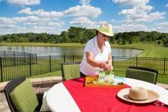 Senior lady mixing refreshing summer drinks Royalty Free Stock Photos