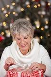 Senior lady opening her Christmas gift royalty free stock photo