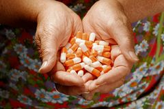 Senior Lady With Palms Full Of Orange-white Pills. Above View Stock Images