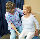 Senior Lady and Physical Therapist. Physical therapist helps a senior woman exercise using a pilates ball Royalty Free Stock Photos