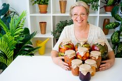 Senior lady with pickled food. Vegetables cucumbers tomatoes Stock Photo