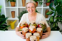 Senior lady with pickled food. Vegetables cucumbers tomatoes Stock Image