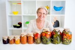 Senior lady with pickled food. Vegetables cucumbers tomatoes Stock Photos