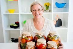 Senior lady with pickled food. Vegetables cucumbers tomatoes Royalty Free Stock Photo