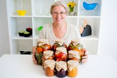 Senior lady with pickled food. Vegetables cucumbers tomatoes Stock Photography