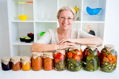 Senior lady with pickled food. Vegetables cucumbers tomatoes Royalty Free Stock Photos
