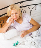 Senior lady with pills  in bed Stock Image