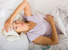 Senior lady with pills and towel compress Royalty Free Stock Photos