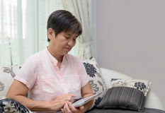 Senior lady playing tablet pc. Portrait of Asian elderly lady using notepad Royalty Free Stock Images