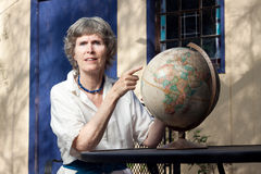 Senior lady pointing at a map (globe). Mature woman pointing at where she wants to go traveling. Exploration of the planet theme stock photo