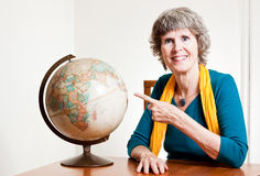 Senior lady pointing to a map of the earth Stock Images